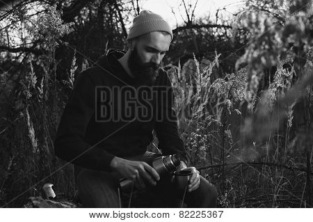 bearded lumberjack pours tea from a thermos