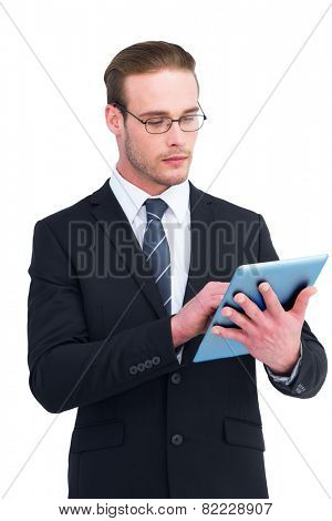 Unsmiling businessman using tablet pc on white background