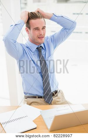 Stressed businessman sitting at his desk in his office