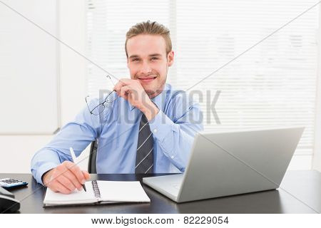 Smiling businessman taking notes on notebook in his office