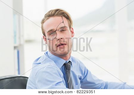 Tired businessman with glasses waking up in his office