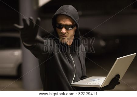Hacker in balaclava gesturing and using laptop on shadowy background
