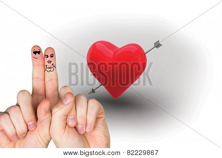 Fingers crossed like a couple against red heart