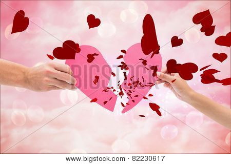 Hands holding two halves of broken heart against digitally generated pink girly design