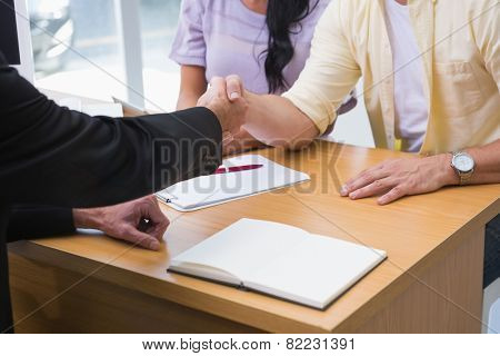Close up of salesman shaking a customer hand at new car showroom