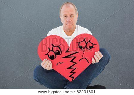 Upset man sitting holding heart shape against grey