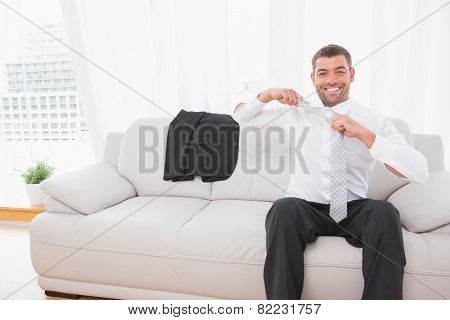 Businessman taking off his tie in his sofa