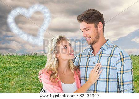 Attractive young couple smiling at each other against road on grass