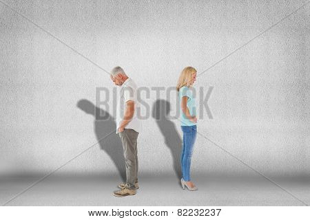 Unhappy couple not speaking to each other against grey wall