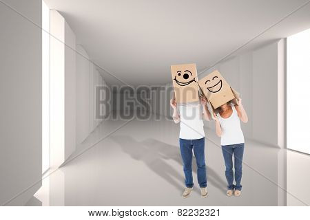 Mature couple wearing boxes over their heads against digitally generated room with bright light