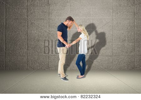 Angry man overpowering his girlfriend against grey room