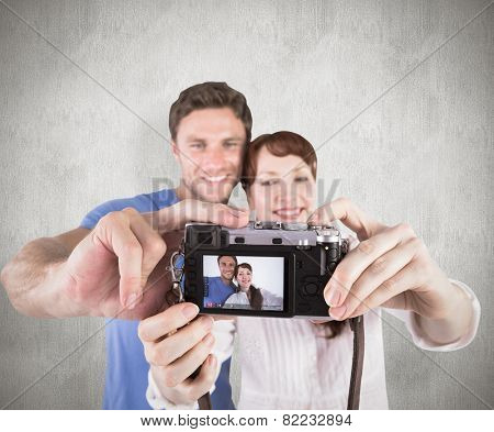 Couple using camera for picture against weathered surface