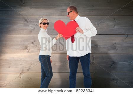 Older affectionate couple holding red heart shape against bleached wooden planks background