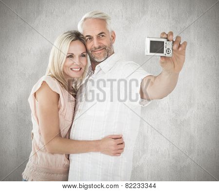 Happy couple posing for a selfie against weathered surface