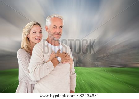 Happy couple standing and hugging against cloudy sky over city