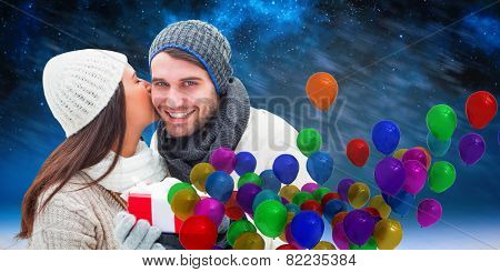 Winter couple holding gift against aurora night sky in blue
