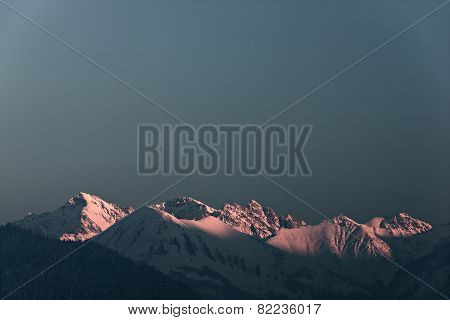 highlighted snowy mountain summits in austria at sunset