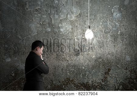 Businessman Pondering With Brightly Light Bulb Illuminated Dark Concrete Wall
