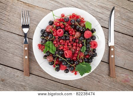 Fresh ripe berries plate on wooden table background