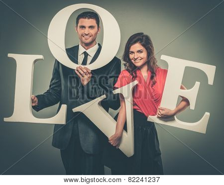 Couple holding word LOVE made from foam plastic