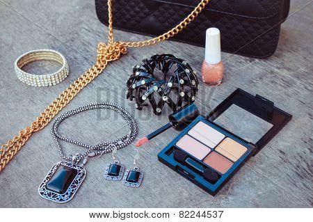 Women's accessories: eyeshadow, lip gloss, nail polish, clip hair, necklace, black handbag. Toned im