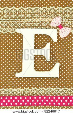 Wooden letter E on polka dots background