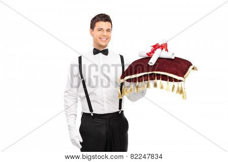 Butler holding a red pillow with two University diplomas isolated on white background