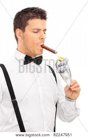 Vertical shot of a rich man lighting up a cigar with burning dollar isolated on white background