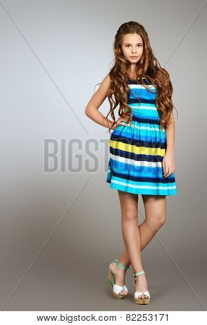 Full length portrait of a beautiful smiling girl teenager with long curly hair posing in bright summer dress. Studio shot.