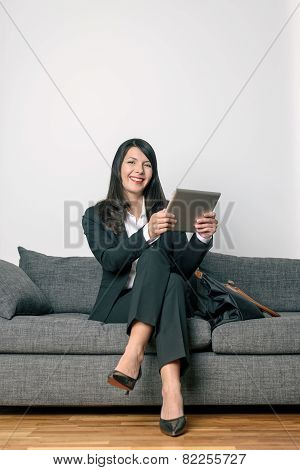 Businesswoman Sitting Reading A Tablet-pc