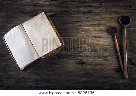Old open book without  text  old wooden spoon on a wooden table