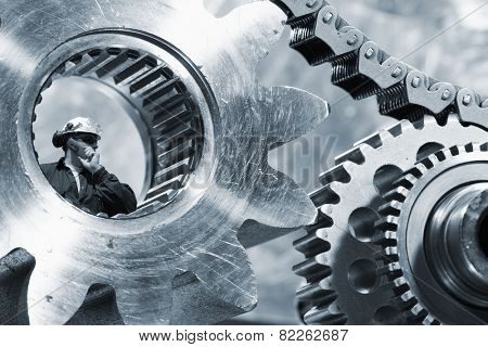 engineer, mechanic seen through a large cogwheels axle and chain