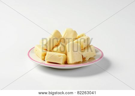 plate of milk toffee candies on white background