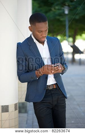 African Businessman Sending Text Message On Mobile Phone