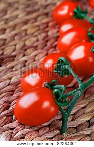tomatoes bunch closeup on straw background