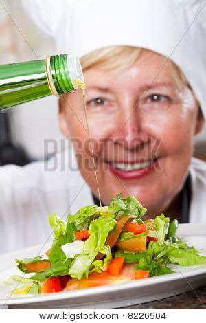 chef pouring olive oil on salad
