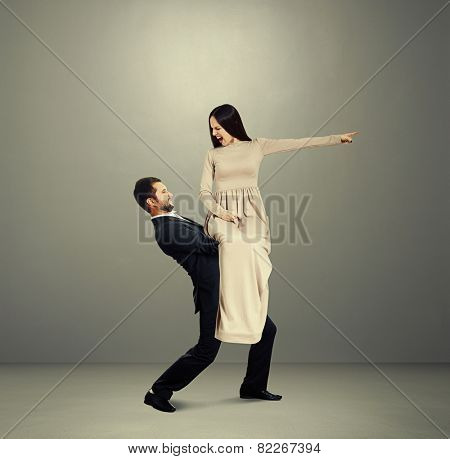 dissatisfied young woman in long dress sitting on tired man, pointing at something and screaming. photo over grey background