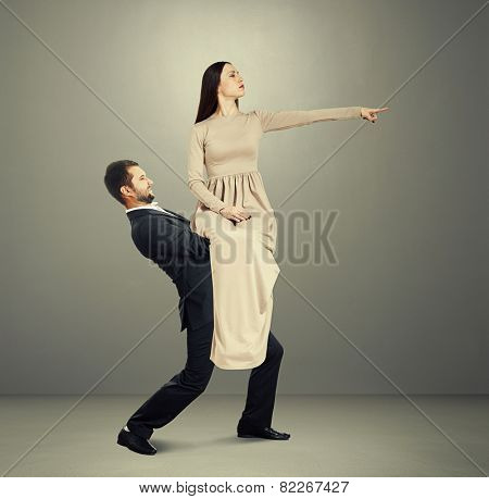 serious young woman sitting on tired man and pointing at something. photo in grey room