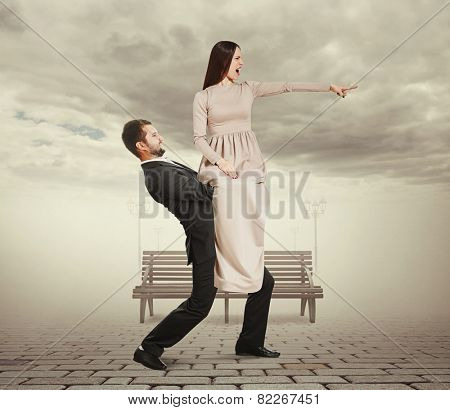 angry screaming woman sitting on tired man and pointing at something. photo at outdoor