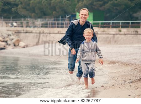 Little Boy Running With His Father At The Surf Line