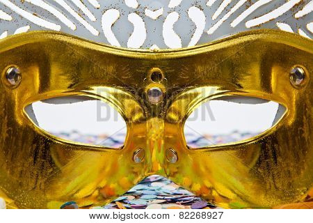 Hidden behind the golden mask on a Carnival party on white background