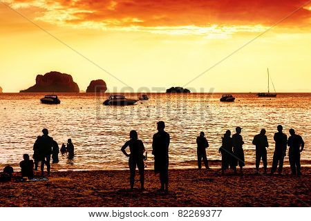 Silhouettes Of Unknown People Watching Red Sunset.