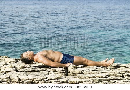 A man sunbathing on rocks