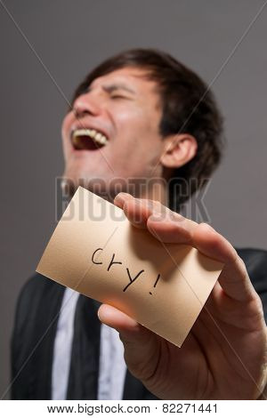 Asian businessman holding card in studio.