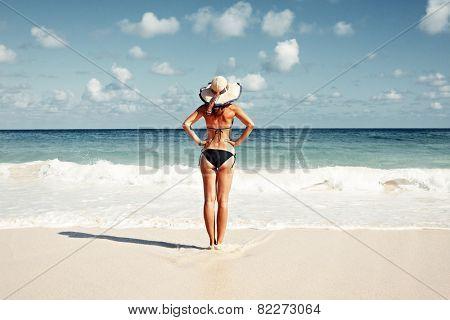 Woman in bikini and hat on tropical beach