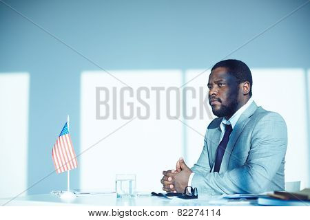 African-american employer sitting by desk