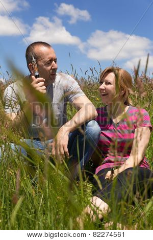 Couple With E-cigarette In A Meadow