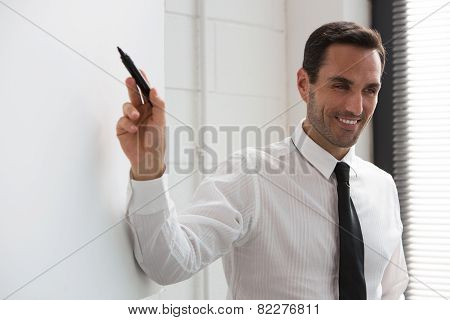 businessman smiling at camera and wrtiting on a blank billboard