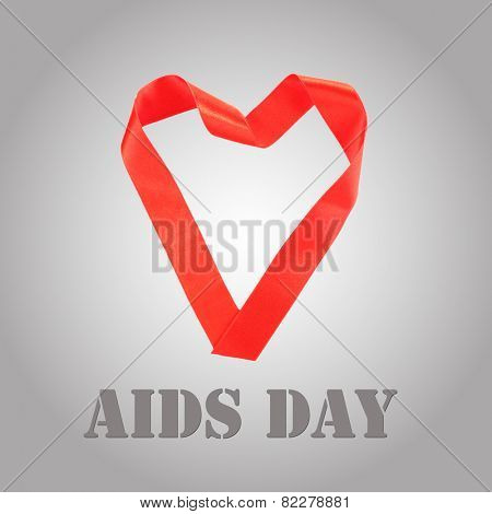 Heart shaped red ribbon on grey background