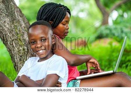 African Kids Under Tree With Laptop.